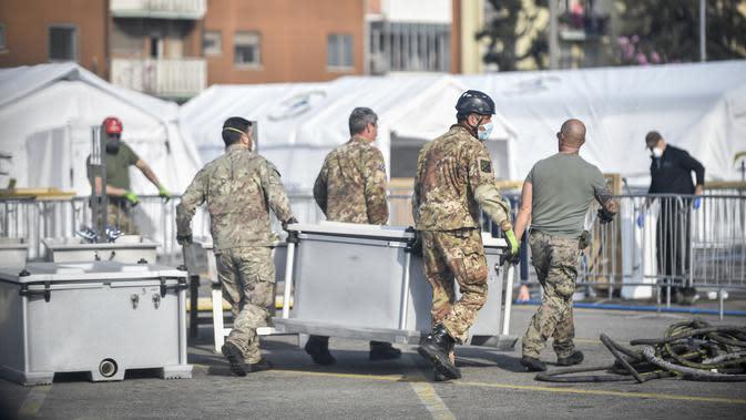 Tentara membawa peralatan rumah sakit lapangan darurat Samaritan's Purse di Cremona, Italia, Jumat, 20 Maret 2020. Rumah sakit lapangan ini dibangun untuk merawat pasien virus corona COVID-19 yang terus melonjak. (Claudio Furlan/LaPresse via AP)