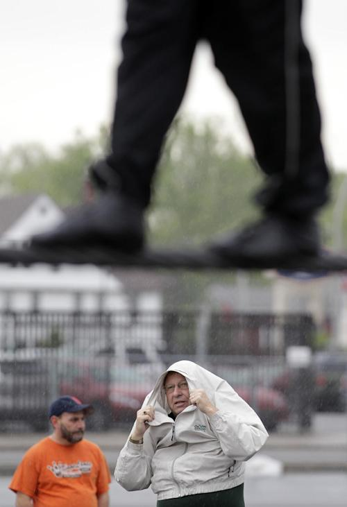 FILE - This May 16, 2012 photo shows Nik Wallenda performing a walk on a tightrope in the rain as people watch during training for his walk over Niagara Falls in Niagara Falls, N.Y. Wallenda can't visit a new place without envisioning a wire strung high above his head: Linking buildings, landmarks, nations. Even as a 6-year-old at Niagara Falls with his parents, he pictured walking a tightrope over the raging, whitewater maw. Now 33, he's ready to live out that childhood fantasy when he attempts Friday, June 15, 2012 to become the first person ever to walk a tightrope directly over the brink of Niagara Falls. (AP Photo/David Duprey)