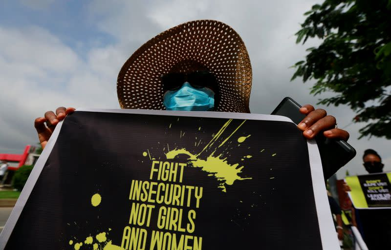 A protester carries a banner during a demonstration to raise awareness about sexual violence, in Abuja