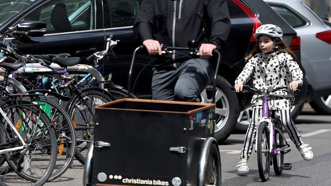 Seorang anak mengendarai sepeda di sebuah jalan di Wina, Austria, (13/5/2020). Menurut Transport Club Austrian, semakin banyak warga Wina memilih bepergian menggunakan sepeda selama pandemi. (Xinhua/Guo Chen)