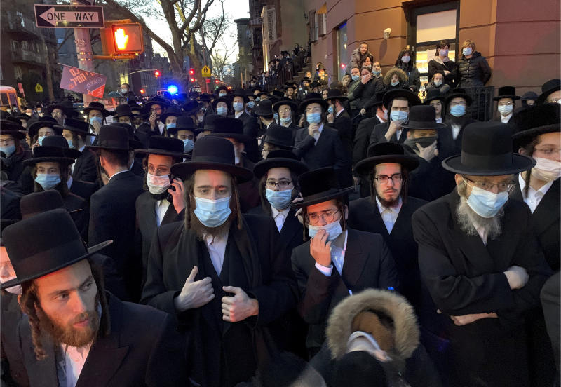 FILE- In this April 28, 2020 file photo, hundreds of mourners gather in the Brooklyn borough of New York, to observe a funeral for Rabbi Chaim Mertz, a Hasidic Orthodox leader whose death was reportedly tied to the coronavirus. On Friday, June 26, 2020, a federal judge in New York blocked the state from enforcing coronavirus restrictions limiting indoor religious gatherings to 25% capacity when other types of gatherings are limited to 50%. Restrictions limiting the number of people who can attend outdoor religious gatherings will also be lifted by the injunction. (Peter Gerber via AP, File)