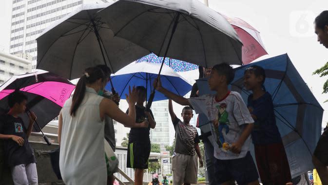 Sejumlah anak-anak menawarkan jasa ojek payung kepada warga di kawasan Bundaran HI, Jakarta, Senin (3/2/2020). Hujan deras yang mengguyur sejumlah wilayah di DKI Jakarta dimanfaatkan para pengojek payung untuk mencari penghasilan tambahan. (Liputan6.com/Angga Yuniar)