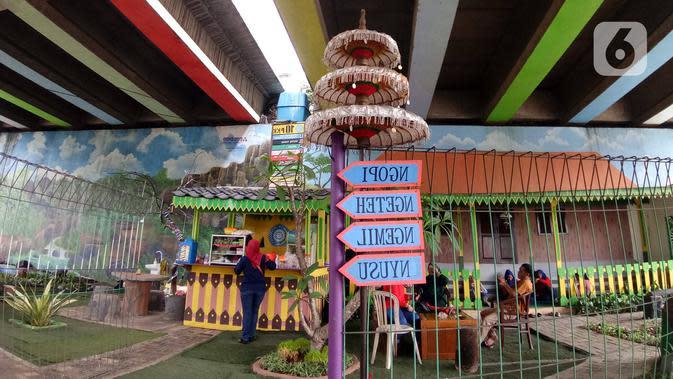 Warga beraktivitas di Taman Betawi Bale Joglo yang terletak di kolong tol JORR W2, Joglo, Jakarta, Senin (13/1/2020). Bale joglo adalah kantin di bawah kolong tol Joglo yang dimanfaatkan sebagai tempat untuk berjualan makanan khas Betawi. (Liputan6.com/Angga Yuniar)