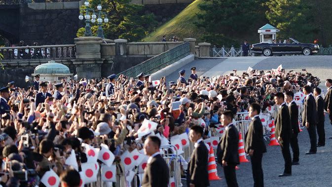 Ribuan warga menyaksikan parade Kaisar Naruhito dan Permaisuri Masako di Tokyo, Jepang, Minggu (10/11/2019). Warga datang sejak pagi agar mendapatkan tempat terbaik untuk menyaksikan parade tersebut. (AP Photo/Eugene Hoshiko)