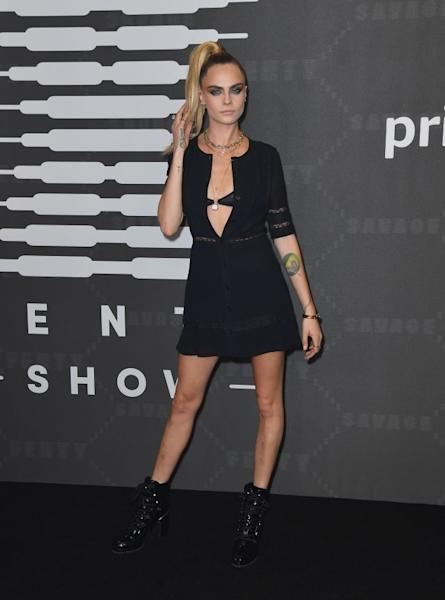 Cara Delevingne in a little black dress left partially open to show a hint of lace bra. New York, September 10, 2019