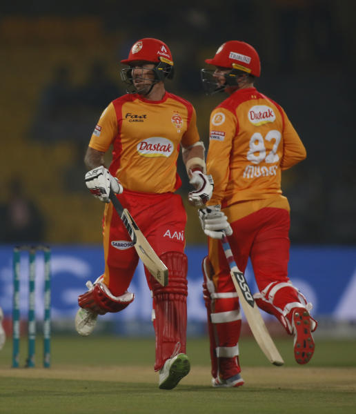 Colin Munro, right, of Islamabad United runs between the wickets with his teammate Luke Ronchi, playing against the Lahore Qalandars during a Pakistan Super League T20 match in Lahore, Pakistan, Wednesday, March 4, 2020. (AP Photo/K.M. Chaudary)