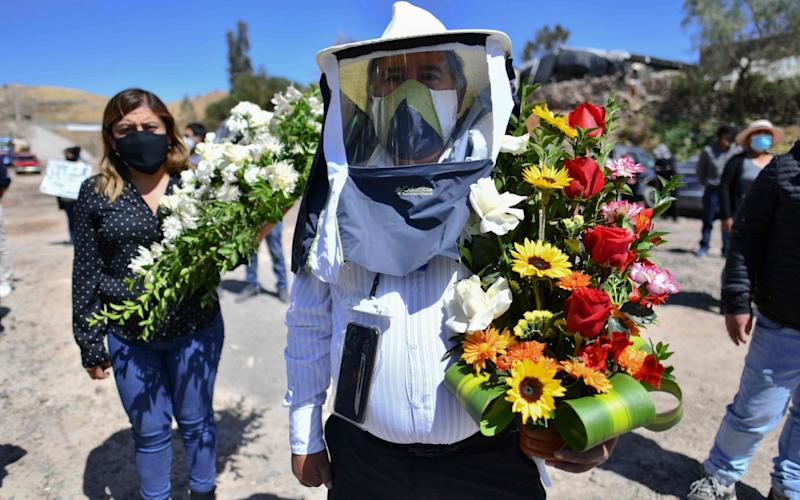 Residents of the rural community of Yura, close to the city of Arequipa, in southern Peru, participate in the burial of their mayor Angel Benavente, with an outdoor mass and an animated funeral possession - Diego Ramos / AF