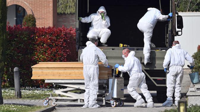 Petugas membawa peti mati berisi jasad korban virus corona COVID-19 yang diturunkan dari truk militer di pemakaman Ferrara, Italia, Sabtu (21/3/2020). Konvoi truk militer membawa korban meninggal COVID-19 dari Bergamo, kota pusat penyebaran COVID-19 di Italia. (Massimo Paolone/LaPresse via AP)