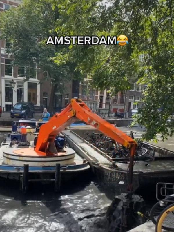 Petugas mengangkut bangkai sepeda di kanal sungai Amsterdam.