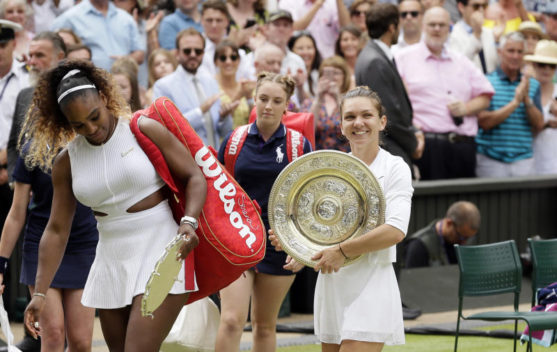 FILE - In this July 13, 2019, file photo, Romania's Simona Halep walks away with her trophy after defeating  Serena Williams, left, in the women's singles final match on day twelve of the Wimbledon Tennis Championships in London. (AP Photo/Tim Ireland, File)