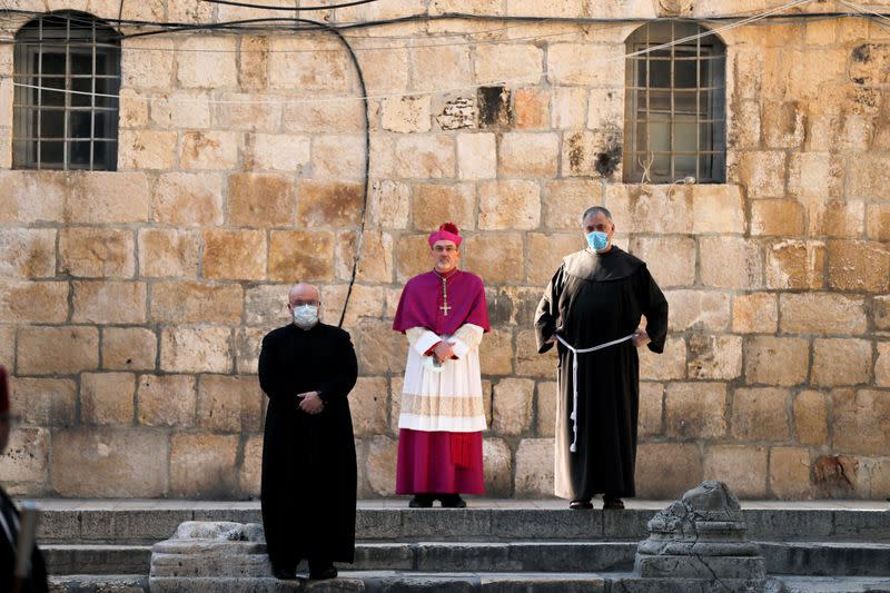 FILE PHOTO: Archbishop Pierbattista Pizzaballa, apostolic administrator of the Latin Patriarchate of Jerusalem stands at the entrance to the Church of the Holy Sepulchre amid coronavirus restrictions in Jerusalem's Old City