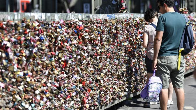 Warga melewati gembok cinta di sebuah jembatan di Cologne, Jerman, Rabu, (5/8/2020). Sebagai bukti cinta mereka, puluhan ribu pasangan telah memasang gembok selama bertahun-tahun ke pagar di Jembatan Hohenzollern sebelum melemparkan kunci ke dalam Sungai Rhein di bawah. (AP Photo/ Martin Meissner)