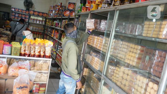 Pembeli memilih kue kering di salah satu toko penjualan kue kering di kawasan Ciracas, Jakarta, Selasa (19/5/2020). Adanya pandemi covid-19 diakui para pedagang menyebabkan penjualan kue kering menjelang lebaran turun hingga 50 persen. (Liputan6.com/Immanuel Antonius)