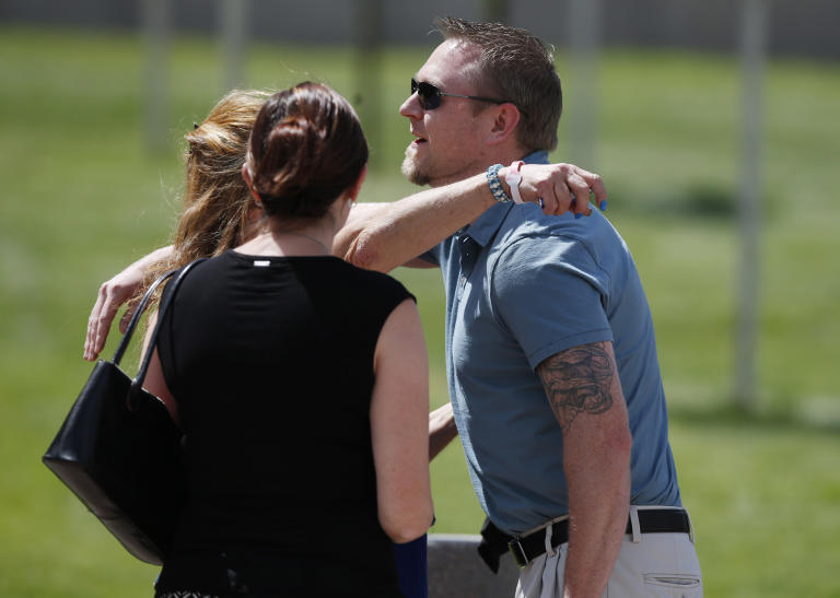Josh Nowlan, right, one of the victims in the 2012 theater shootings in Aurora, Colo., is hugged as he heads in to hear the verdict against James Holmes as the trial concluded Thursday, July 16, 2015, in Centennial, Colo. The 27-year-old Holmes, who had been working toward his Ph.D. in neuroscience, could get the death penalty for the massacre that left 12 people dead and dozens of others wounded on July 20, 2012. (AP Photo/David Zalubowski)