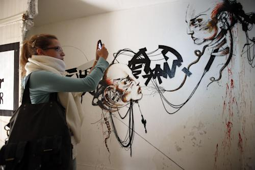 A visitor takes a picture of an installation in a social housing tower converted into a temporary street art exhibition in Paris, France, Tuesday, Oct. 8, 2013. Condemned apartments never looked so good _ and only rarely has graffiti met such an enthusiastic welcome. More than 80 artists were given free run of a rundown building that is doomed to destruction in 8 days. The line wraps around the block every day to see the apartments, each of which is its own art installation. (AP Photo/Francois Mori)