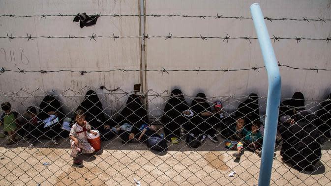Perempuan dan anak-anak keluarga militan ISIS menunggu untuk meninggalkan kamp penampungan al-Hol di Provinsi Hasakeh, Suriah, Senin (3/6/2019). Otoritas Kurdi yang mengelola kamp tersebut membebaskan sekitar 800 perempuan dan anak-anak keluarga militan ISIS. (AP Photo/Baderkhan Ahmad)