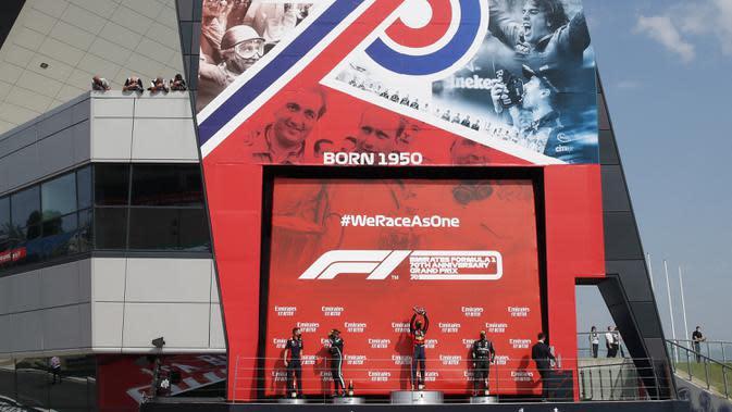 Pembalap Red Bull Max Verstappen (tengah) merayakan kemenangan pada 70th Anniversary Formula 1 Grand Prix di Sirkuit Silverstone, Silverstone, Inggris, Minggu (9/8/2020). Max Verstappen sukses menjadi yang tercepat dalam F1 GP Silverstone 2020. (Andrew Boyers, Pool via AP)