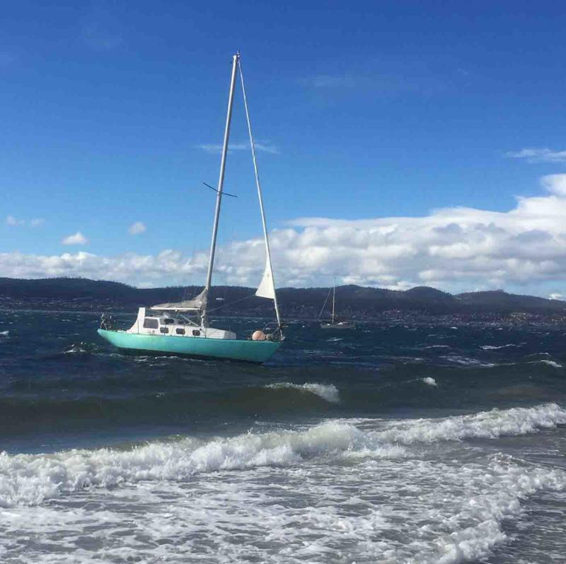 Wild winds forced this boat to break from its moorings at Hobart's Nutgrove Beach, Tasmania.