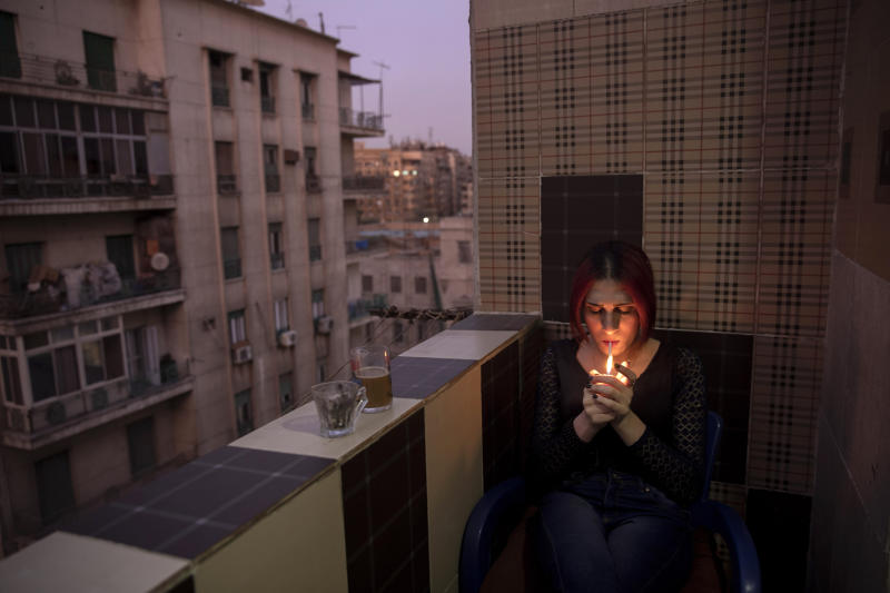 In this Oct. 28, 2019 photo, Egyptian transgender woman and activist Malak el-Kashif smokes a cigarette in the balcony of her apartment in Cairo, Egypt. She has been ostracized by her family and scorned by some who accuse her of tampering with God's creation. She has been attacked by others scandalized by her activism for LGBTQ rights. Legally, she still holds a male's identity card. (AP Photo/Nariman El-Mofty)