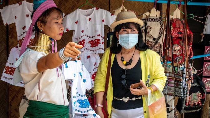 Perempuan Suku Kayan berbicara dengan turis yang mengenakan masker di sebuah toko suvenir di Taman Chang Siam, Pattaya, Thailand, Rabu (12/2/2020). Chang Siam Park adalah salah satu primadona bagi wisatawan China di Pattaya yang kini berangsur sepi karena virus corona. (Mladen ANTONOV / AFP)