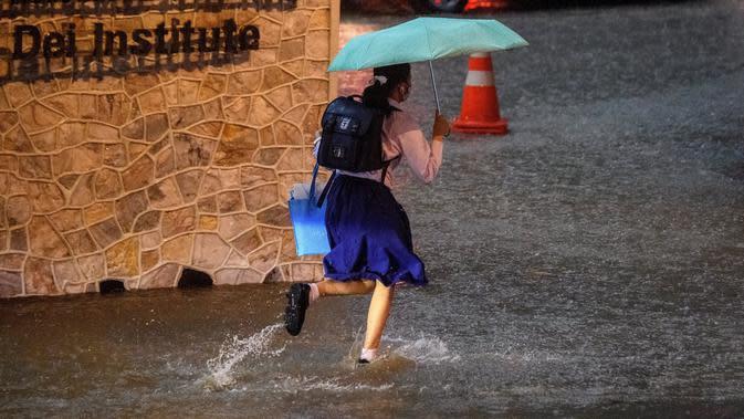 Seorang gadis sekolah berlari di jalan yang sebagian tergenang air saat hujan deras di Bangkok (23/9/2020). (AFP/Mladen Antonov)