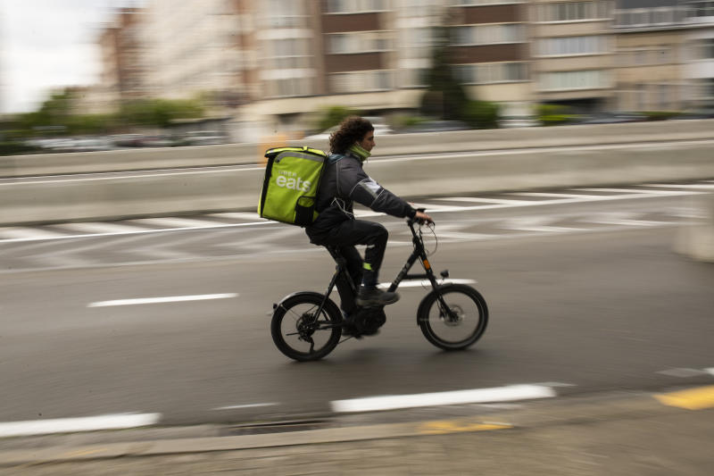 A food delivery carrier rides a bicycle along a newly path designated only for bikes, during a gradual lifting of a lockdown to prevent the spread of the coronavirus, COVID-19, in Brussels, Monday, May 4, 2020. As European cities gradually relax lockdown measures, Brussels authorities intend to take advantage of the coronavirus health crisis to turn the EU institutions capital into a cycling-friendly greener place. (AP Photo/Francisco Seco)