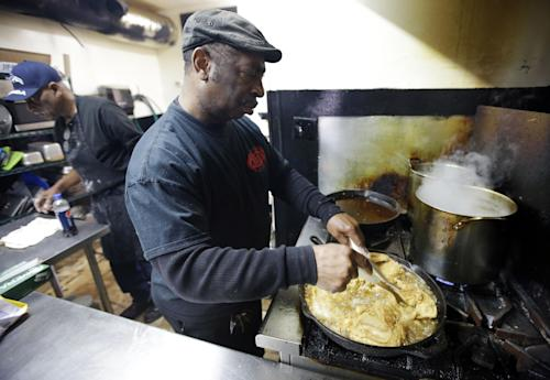 In this Friday, March 22, 2013 photo, Bolton Matthews fries chicken at Bolton's Spicy Chicken and Fish restaurant in Nashville, Tenn. Hot chicken -- fried chicken with varied amounts of seasoning that make the heat level run from mild to extra hot -- is a signature dish of Nashville. (AP Photo/Mark Humphrey)