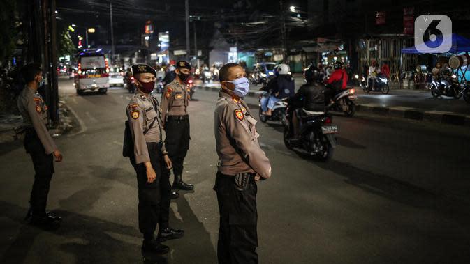 Polisi berjaga pada malam takbiran di Jalan KH Mas Mansyur, Jakarta, Sabtu (23/5/2020). Polisi dikerahkan menjaga Jalan KH Mas Mansyur untuk mengantisipasi adanya takbir keliling di kawasan tersebut. (Liputan6.com/Faiza Fanani)