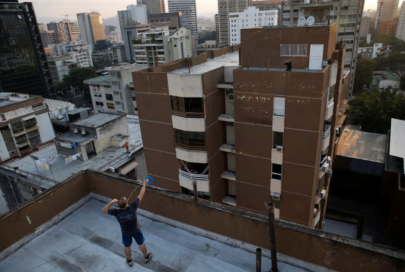 Francisco throws a plastic container filled with wine to another rooftop during a nationwide quarantine due to the coronavirus disease (COVID-19) outbreak in Caracas