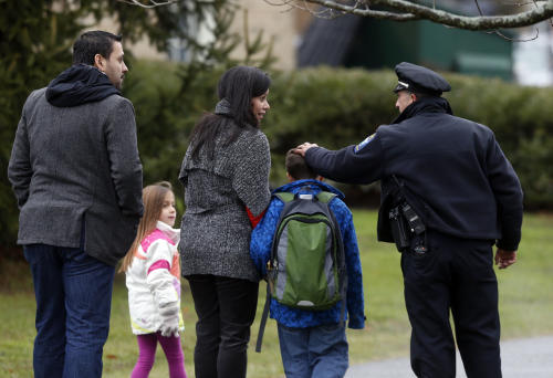 Easton police officer J. Sollazzo greets a returning student as he is walked into Hawley School in Newtown, Conn., Tuesday, Dec. 18, 2012. Classes resumed Tuesday for Newtown, schools except those at Sandy Hook, following Friday's mass shooting at the Sandy Hook Elementary School. Buses ferrying students to schools were festooned with large green and white ribbons on the front grills, the colors of Sandy Hook. At Newtown High School, students in sweatshirts and jackets, many wearing headphones, betrayed mixed emotions. (AP Photo/Jason DeCrow)
