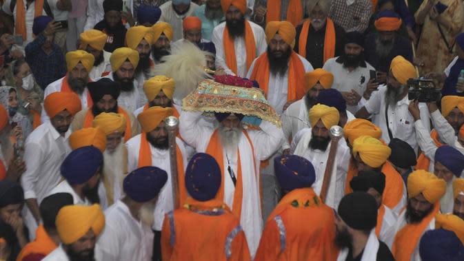 Kepala pendeta Sikh Jagtar Singh (tengah) membawa teks pokok agama Sikhisme, Guru Granth Sahib selama prosesi keagamaan dari Gurudwara Ramsar ke Akal Takht Sahib di Kuil Emas, Amritsar, India, Rabu (19/8/2020). Acara ini untuk memperingati 416 tahun pelantikan Guru Granth Sahib. (NARINDER NANU/AFP)