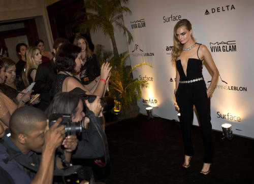 British model Cara Delevingne poses for photographers as she arrives to a charity dinner for amfAR, a foundation for AIDS research in Rio de Janeiro, Brazil, Friday, Oct. 4, 2013. (AP Photo/Silvia Izquierdo)