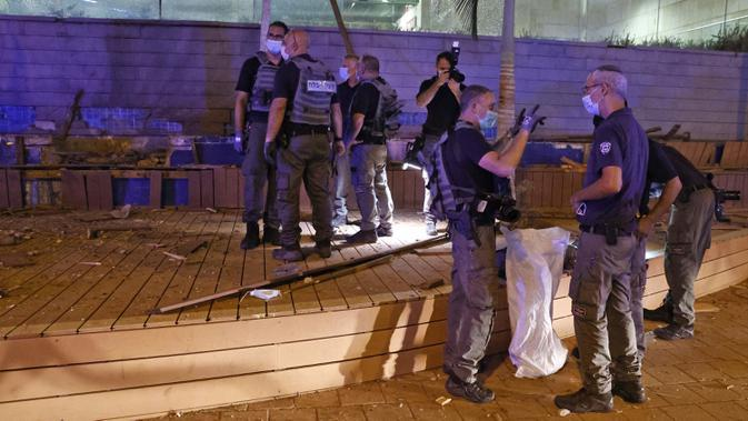Pasukan keamanan Israel memeriksa lokasi serangan roket dari Jalur Gaza yang jatuh di Kota Ashdod, Selasa (15/9/2020). Serangan yang terjadi saat Israel menandatangani kesepakatan normalisasi dengan Bahrain dan UEA ini mengakibatkan dua orang terluka. (JACK GUEZ/AFP)