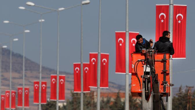 Buruh memasang bendera di tiang listrik menuju perbatasan Oncupinar di Kota Kilis, Turki, Senin (29/1). Bentrokan sempat meletus di puncak bukit strategis di Suriah karena milisi Kurdi mencoba mendapatkan kembali kontrol. (AP Photo/Lefteris Pitarakis)