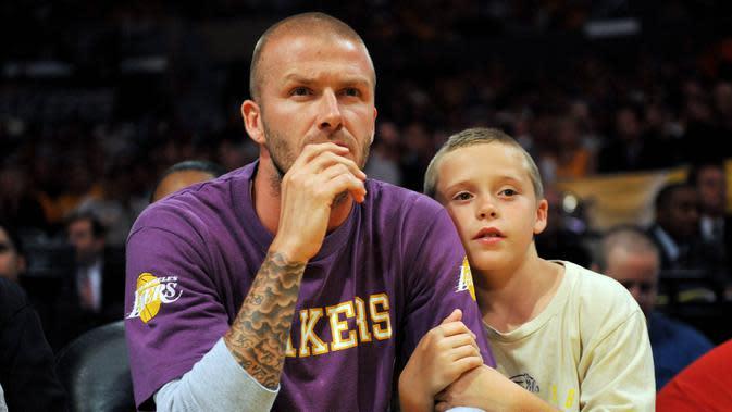 Legenda Timnas Inggris, David Beckham, bersama anaknya, Brooklyn, saat menyaksikan pertandingan NBA antara Boston Celtics melawan Los Angeles Lakers di Amerika Serikat, (10/6/2008). (Photo by GABRIEL BOUYS / AFP)