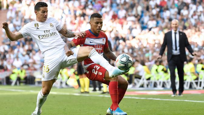 Gelandang Real Madrid, James Rodriguez, berebut bola dengan striker Granada, Darwin Machis, pada laga La Liga Spanyol di Stadion Santiago Bernabeu, Madrid, Sabtu (5/10). Madrid menang 4-2 atas Granada. (AFP/Pierre-Philippe Marcou)