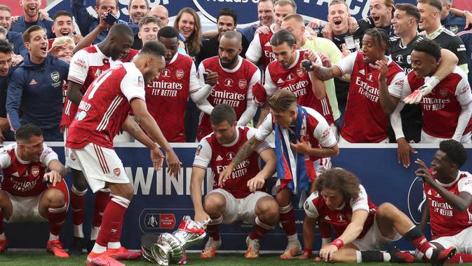 Striker Arsenal, Pierre-Emerick Aubameyang menjatuhkan trofi saat perayaan gelar juara Piala FA usai mengalahkan Chelsea pada pertandingan final Piala FA di stadion Wembley, Minggu (2/8/2020). Aubameyang terlihat kaget sambil memegang kepalanya saat trofi terjatuh. (Catherine Ivill/Pool via AP)