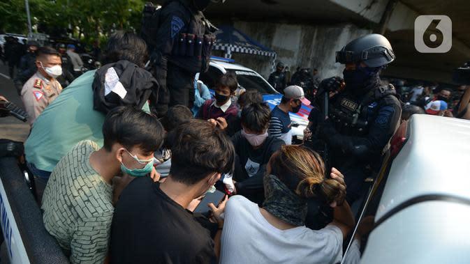 Polisi membawa pelajar yang terjaring razia saat berkumpul di sekitar Gedung DPR/MPR, Jalan Gatot Subroto, Jakarta, Rabu (7/10/2020). Puluhan pelajar diamankan sementara terkait informasi akan adanya demo dari media sosial. (merdeka.com/Imam Buhori)