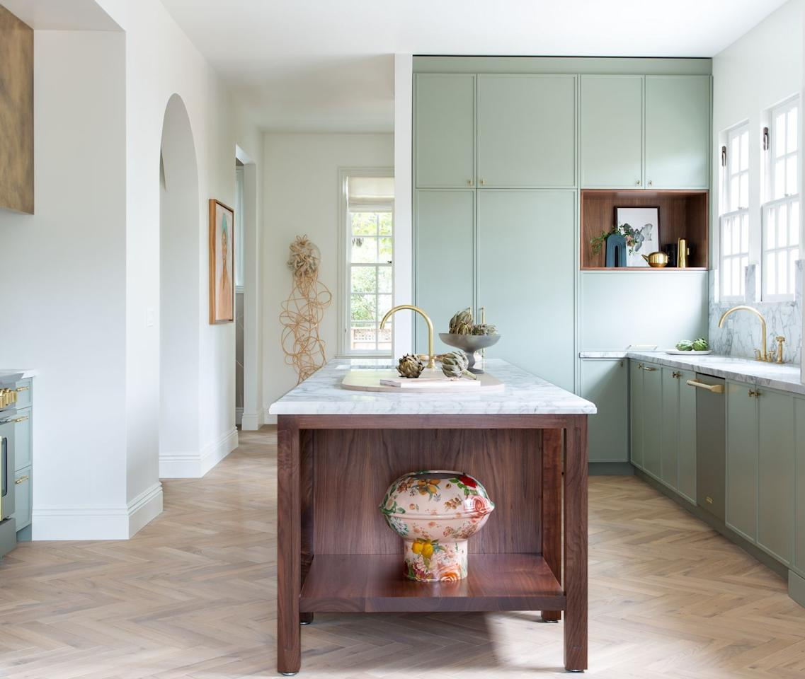 """<p>The goal for this kitchen by <a href=""""https://reganbakerdesign.com/"""" target=""""_blank"""">Regan Baker Design</a> was to keep the Mediterranean style and charm of the home intact while blending in an earthy, unsaturated color palette throughout. To complement the interiors—and to address the fact that Black artists and designers have been underrepresented in the past—Baker chose to display artworks from Black female artists (<a href=""""https://www.christadavid.com/"""" target=""""_blank"""">Christa David</a>, <a href=""""https://www.musebymarie.com/"""" target=""""_blank"""">Marie Alexander</a>, <a href=""""https://www.ladynoeldesigns.com/"""" target=""""_blank"""">Lauren Pearce</a>, and <a href=""""https://www.tawnychatmon.com/"""" target=""""_blank"""">Tawny Chatmon</a>) that resonated with her and her team. </p>"""