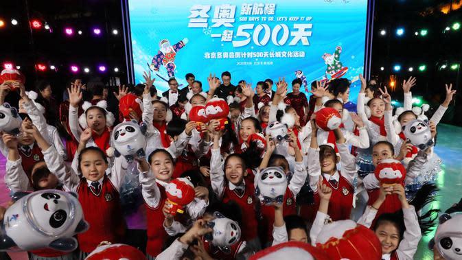 Anak-anak melambaikan tangan sambil memegang maskot Olimpiade dan Paralimpiade Musim Dingin Beijing 2022 dalam kegiatan budaya untuk menyambut hitung mundur 500 hari jelang Olimpiade Musim Dingin Beijing 2022 di Badaling, Distrik Yanqing, ibu kota China, 20 September 2020. (Xinhua/Zhang Chenlin)