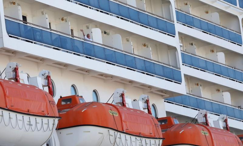 A passenger waves from MSC Fantasia cruise ship in Lisbon