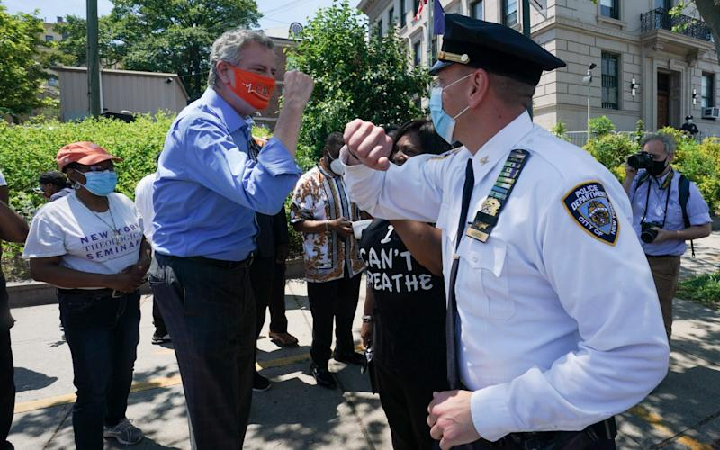 New York Mayor Bill de Blasio greets Inspector Isa Abbassi of the 120th Precinct as New York City's second Black Lives Matter mural is painted by volunteers between Borough Hall and the 120th Precinct in the Borough of Staten Island - AFP