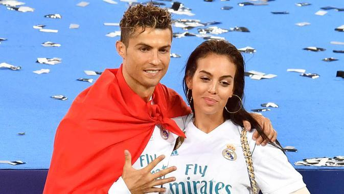 Cristiano Ronaldo bersama kekasihnya, Georgina Rodriguez, berpose usai menjuarai Liga Champions bersama Real Madrid di Stadion Olympic, Kiev (19/5/2019). (AFP/Sergei Supinsky)