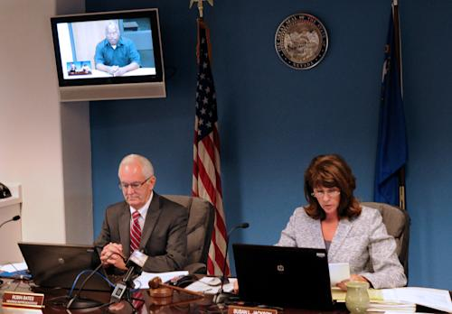 O.J. Simpson, in custody at the Lovelock Correctional Center, is on the video screen above Nevada Board of Parole hearing representative Robin Bates, left, and Commissioner Susan Jackson during a video conference parole hearing, in Carson City, Nev., on Thursday, July 25, 2013. O.J. Simpson pleaded for leniency Thursday, telling the parole panel he deeply regretted robbing two sports memorabilia dealers. (AP Photo/Nevada Appeal, Geoff Dornan)