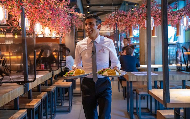 Rishi Sunak, the Chancellor, serving food
