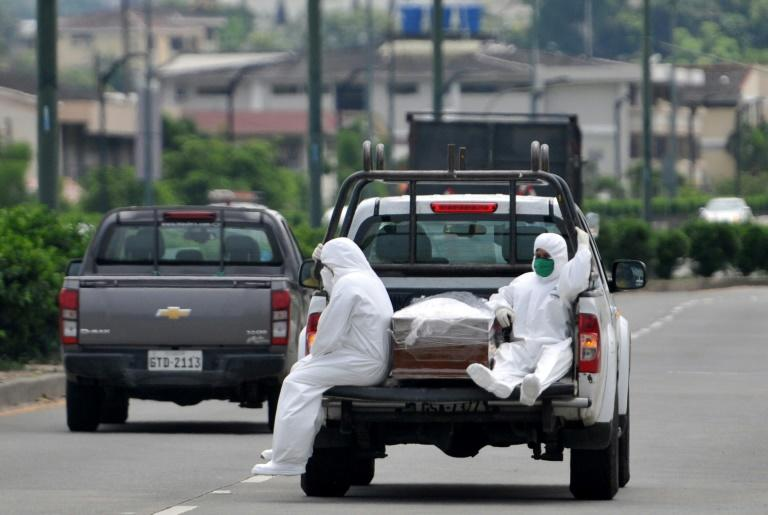 People wearing protective suits accompany a coffin on a truck near Los Ceibos hospital in Guayaquil, Ecuador on April 8, 2020