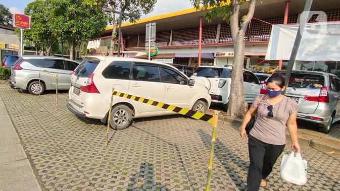 Seorang perempuan melintas di antara mobil yang parkir di Rest Area Km 13,5 di Tol Tangerang, Selasa (19/5/2020). Jelang Lebaran, PT Jasamarga Related Business menerapkan PSBB di semua rest area yang dikelolanya dengan membatasi waktu singgah pengunjung maksimal 30 menit. (Liputan6.com/Angga Yuniar)