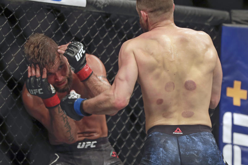 Jeremy Stephens, left, takes a punch from Calvin Kattar during a UFC 249 mixed martial arts bout Saturday, May 9, 2020, in Jacksonville, Fla. (AP Photo/John Raoux)