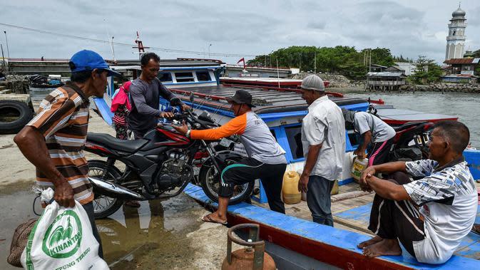 Sejumah pria memuat sepeda motor ke atas kapal saat pulang kampung ke pulau terpencil jelang Idul Fitri di Banda Aceh, Kamis (21/5/2020). Hari Raya Idul Fitri menandai berakhirnya bulan suci Ramadan. (CHAIDEER MAHYUDDIN/AFP)