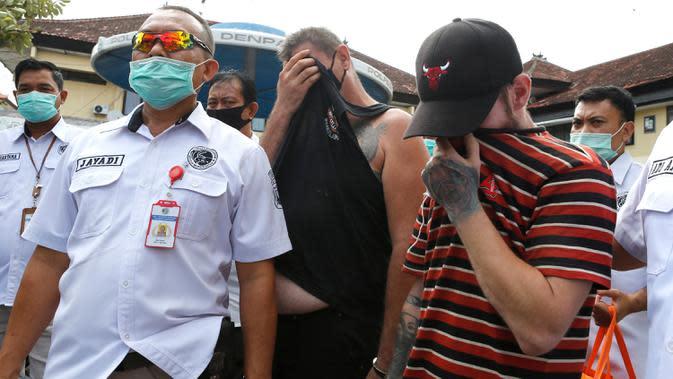 Petugas polisi mengawal Warga Negara Asing (WNA) asal Inggris, Collum (kanan) dan asal Australia, Aaron Wayne Coyle (kedua kanan) di Mapolresta Denpasar, Bali, Kamis (3/9/2020). Kedua WNA tersebut ditahan karena mengedarkan narkoba jenis sabu dan ekstasi di wilayah Bali. (AP Photo/Firdia Lisnawati)